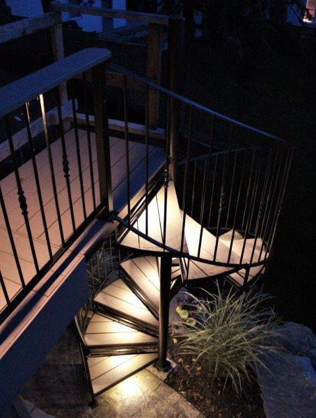 LED lights iron spiral stairs metal circular stairway Trex wood treads wrought iron railing deck lakehouse helix stair