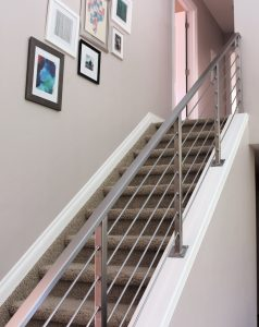 interior horizontal railing down carpet stairs