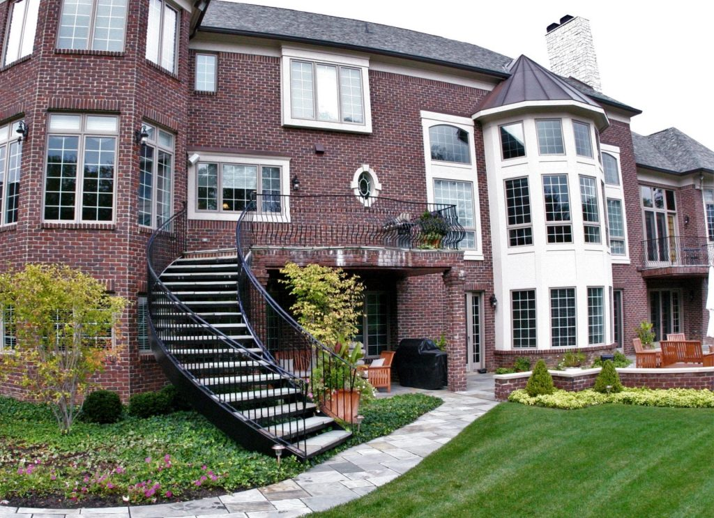 brick home and steel deck installed curved staircase wrought iron railing