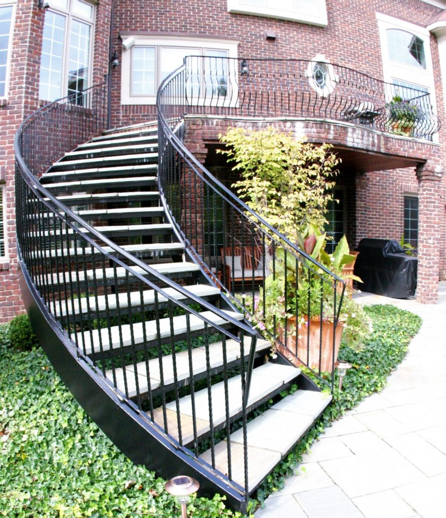 curved staircase curved stairs at brick deck and wrought iron railing