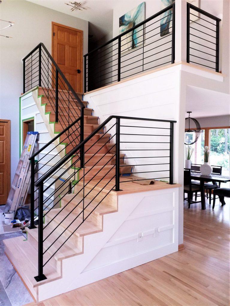 horizontal metal rod railing round bars downstairs wood steps steel top handrail modern interior design contemporary carpet fireplace hardwood
