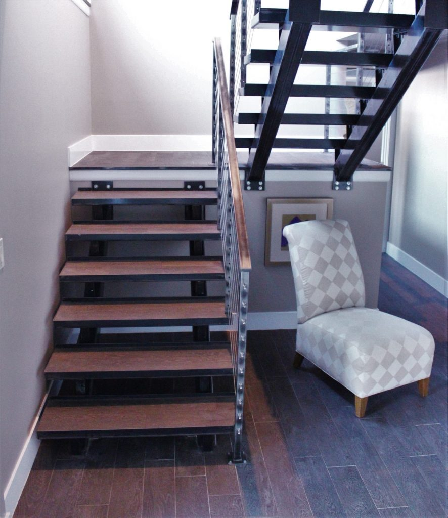 raw steel cable rail industrial style metal stairs floating treads wood floor steel stringer contemporary modern rustic vintage eclectic interior design new construction lake home accent chair basement