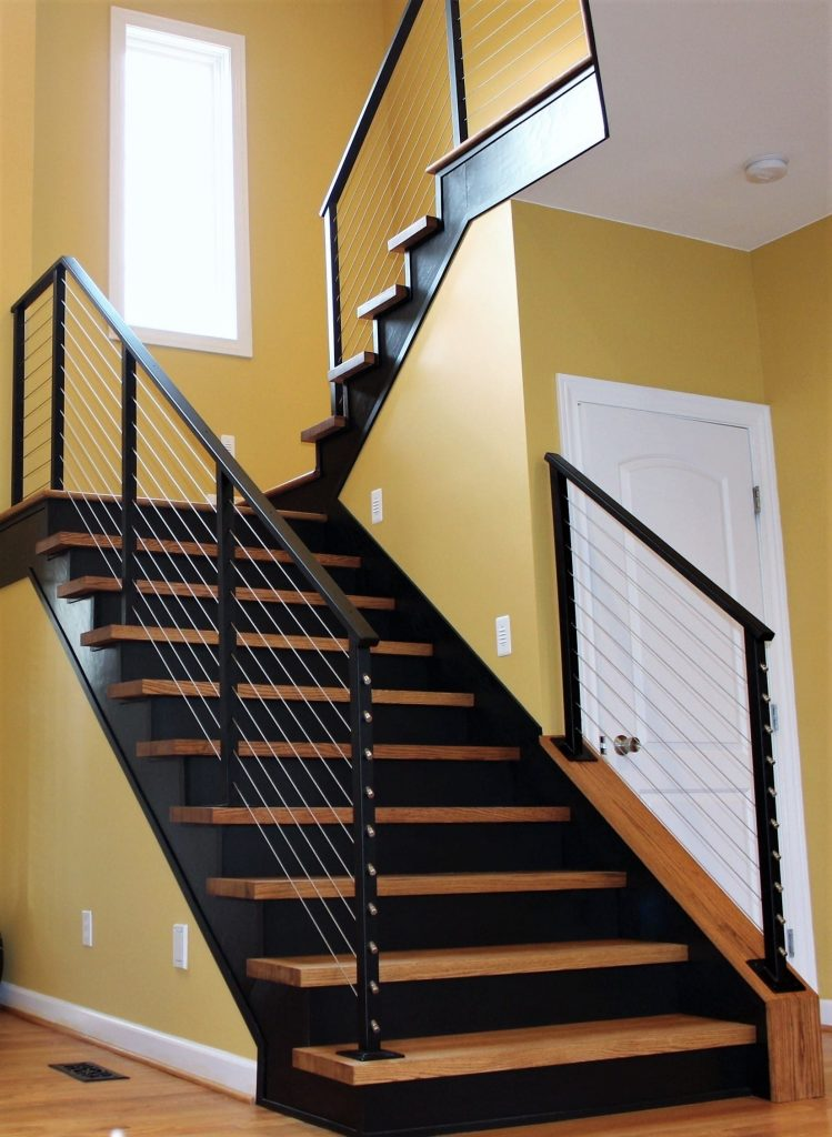 stainless steel cable railing black metal posts wood interior stairs modern interior design remodel yellow paint glass pendant lights second floor bridge