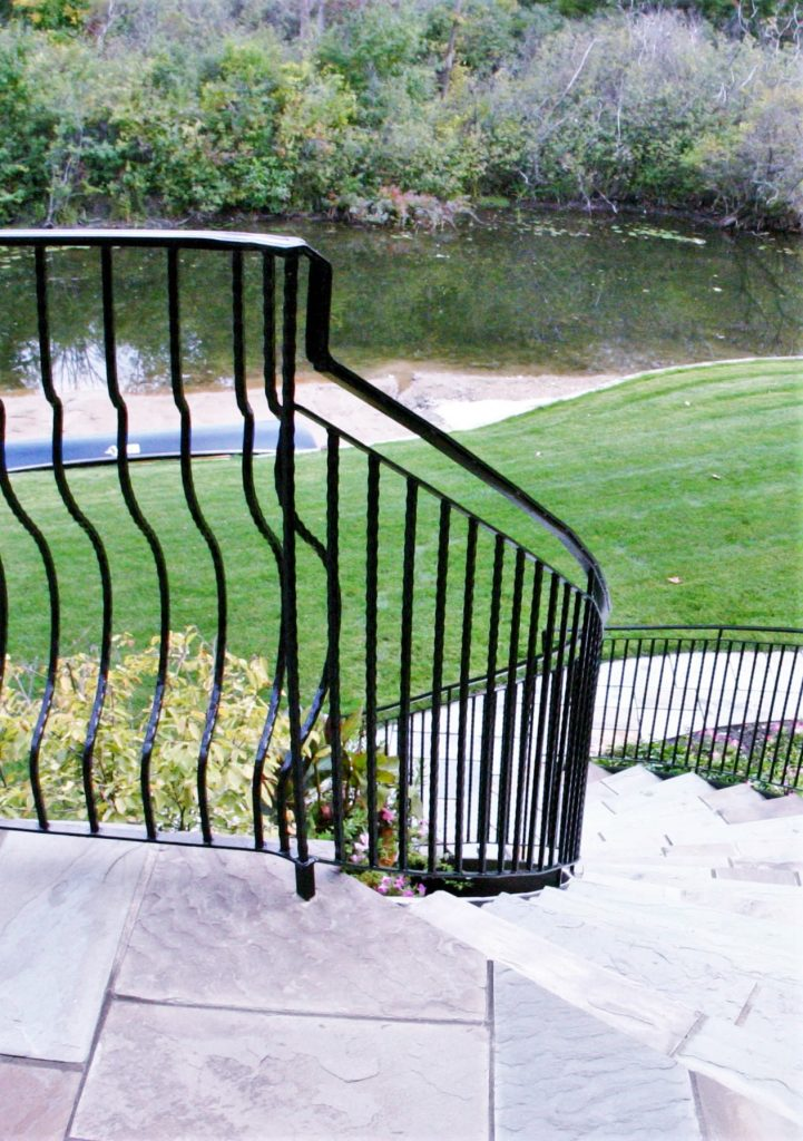 wrought iron metal railing down curved stairs