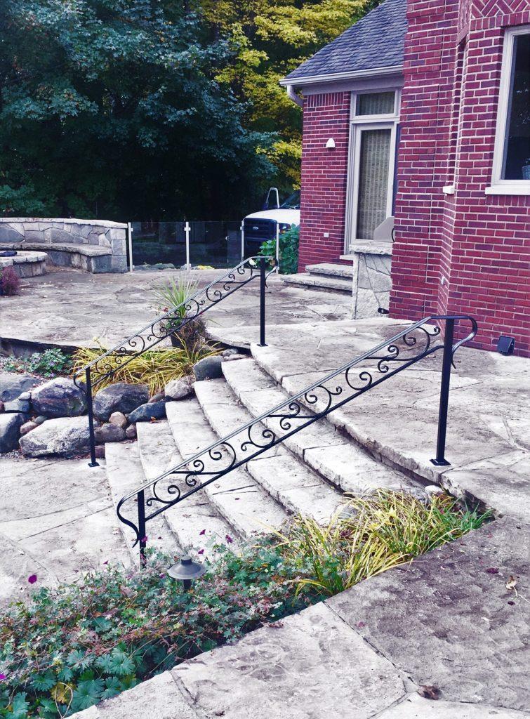 wrought iron handrail scrolls patio steps stone landscape brick home firepit