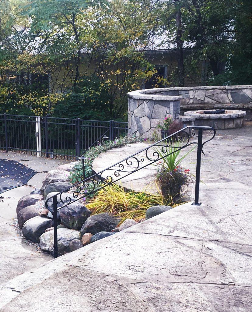 wrought iron railing scroll handrail patio steps stone landscape brick home firepit pool