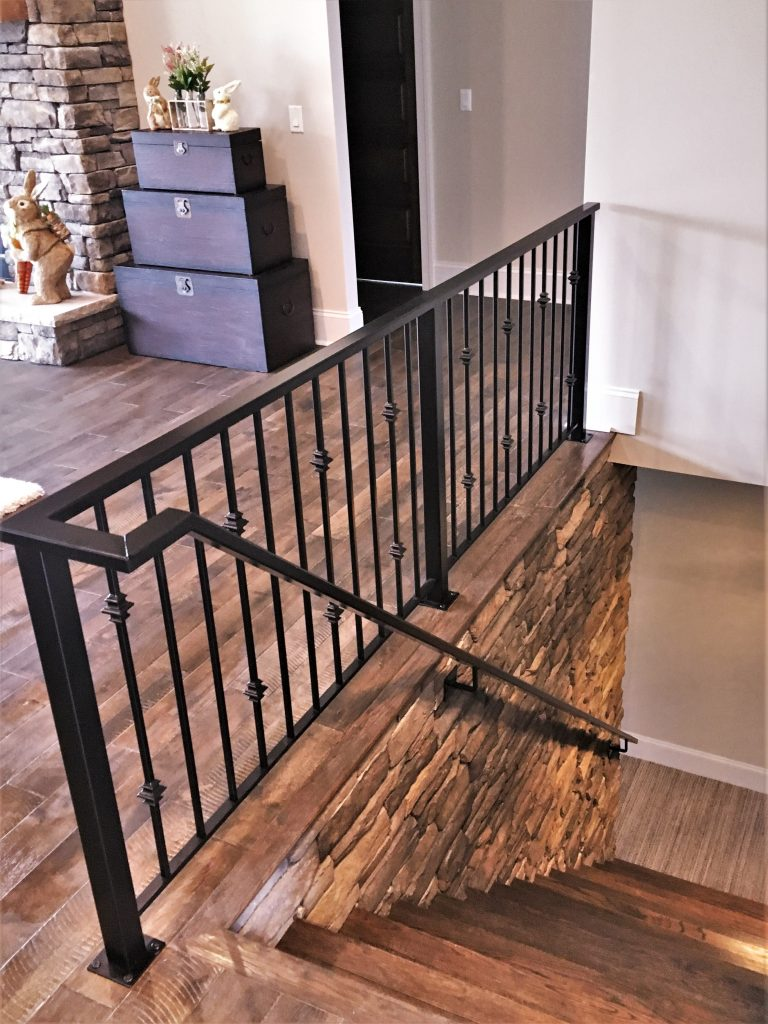 dark bronze wrought iron metal handrail oil rubbed rectangle rail interior stone wall fireplace wood floor square brackets vertical pickets collars knuckles