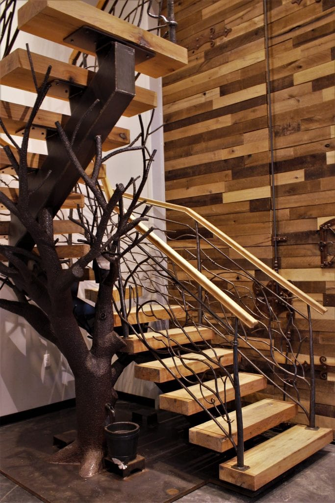 metal tree sculpture steel treetrunk bark texture thick wood treads curved floating steel staircase pallet wall rustic metal railing