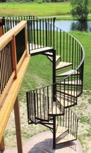 metal gate cedar deck wrought iron spiral stair sunroom brick deck home tall steel spiral staircase curculr stair wood treads metal railing michigan stair contractor